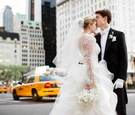 Bride and groom on street in NYC with taxis