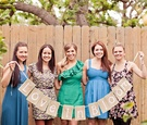 Bride and bridesmaids holding banner sign at bridal shower