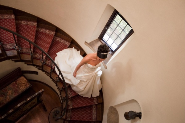 Bride in a Monique Lhuillier gown walks down the stairs