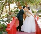 bride and groom kiss on red bridge