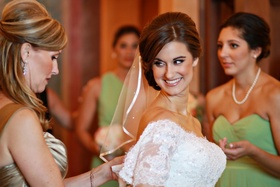 Mother-of-the-Bride buttoning her daughter's gown