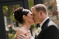 Bride with an updo kisses groom wearing a black tuxedo and orchid boutonniere
