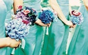 Bridesmaids in blue-green dresses held bouquets