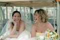 Bride and maid of honor laughing in golf cart