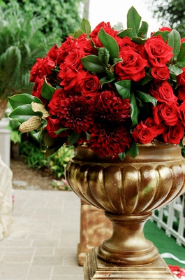 Gold vessel filled with red roses and dahlias