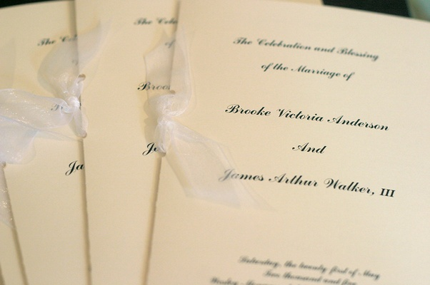 Off-white ceremony booklet with shiny ribbon
