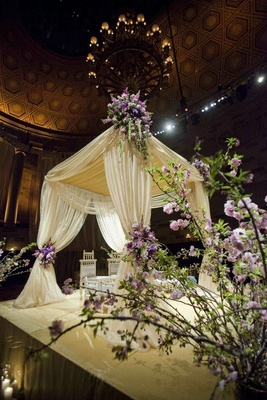 Mandap draped in white fabric and decorated with purple flowers and greenery