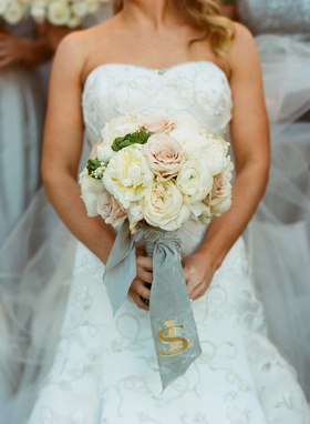 Ivory and pink wedding bouquet tied with monogrammed ribbon