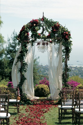 Floral ceremony structure at end of flower petal aisle