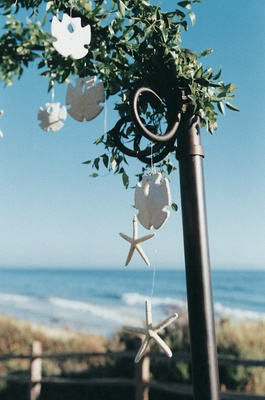 sand dollar and sea star figurines hang from ceremony structure