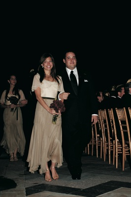 Bridesmaid in long dress with white top and tan skirt with groomsman in black tuxedo and tie