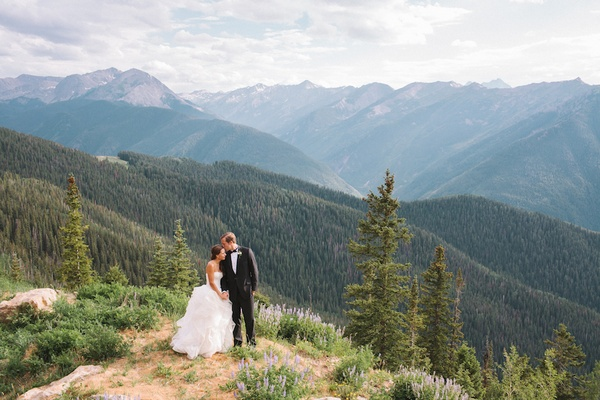 Bride and groom standing on mountain among trees