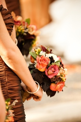 Bridesmaids in bronze dresses holding flowers