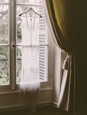 Transparent wedding gown with pearls by Melany Rowe hangs at window of the Chateau de Santeny
