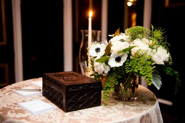 Wooden box on damask linen with anemone flower arrangement