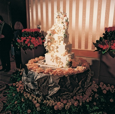 Five tier cake with flowers on table covered with roses