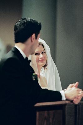 Bride and groom kneeling in church