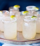 Margaritas in mason jars rimmed with salt and garnished with limes