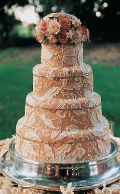 Cake decorated with neutral frosting and white designs