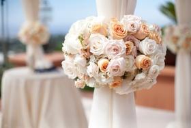 Orange and pink roses around chuppah pillars