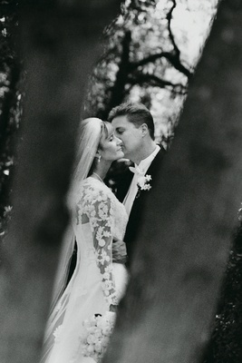 groom kisses bride wearing long sleeved lace wedding gown