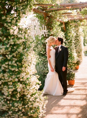 Couple kiss outside under crystal chandelier