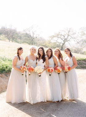 Bride in white dress with bridesmaids in off white gowns
