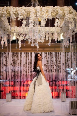 Bride stands underneath chuppah in white dress with black sash