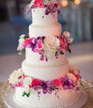 White wedding cake with purple, pink, and white sugar flowers