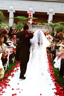 Bride and groom exit among rose petal toss