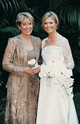 Bride and her mom in front of palm frond