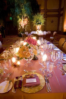 Rectangular table topped with roses and gold plates