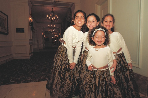Flower girls wearing long-sleeved dresses with a white top, copper skirt, and sash