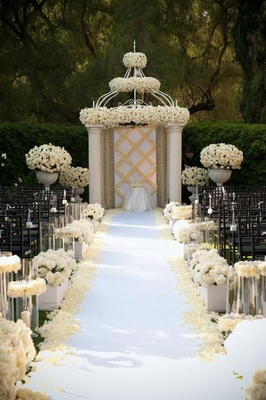 Cream and white roses decorate aisle and canopy