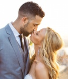 NBA basketball player and bride kissing in sun