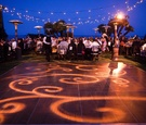 Illuminated dance floor and twinkling lights over tables