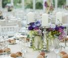 Mercury glass candlesticks next to purple flower centerpiece
