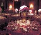 Round reception tables decorated with red, lavender, and fuchsia roses in a tall glass vase