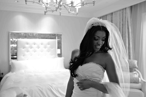 Black and white photo of bride and tufted headboard