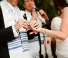 Groom places ring on bride in a Pronovias strapless gown at an outdoor Jewish ceremony