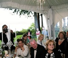 Wedding reception tented area with chandelier and table decorated with crystal candelabra