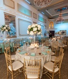 Gilt chairs around guest tables at wedding reception