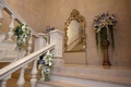 Arrangements of purple, light pink, white flowers adorn stairway at The Plaza for a wedding