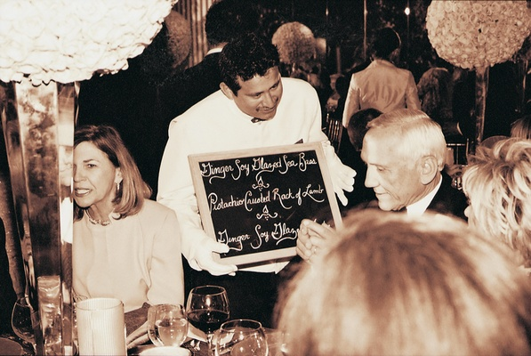 Waiters in white gloves carry chalkboard menus