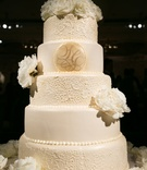White cake with lace details, monogram, and fresh peonies