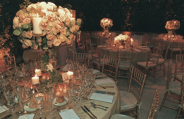 tables featuring tall centerpiece and gold linens