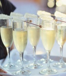 Wedding reception with tray of Champagne flutes and rock candy wands