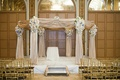 Chuppah draped in light golden fabric decorated with white and blue flower arrangements and crystals