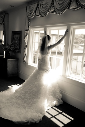 Black and white photo of bride in a fitted Maggie Sottero gown with ruffled skirt and train