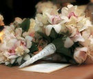 Ivory and pink orchids wrapped in white ribbon